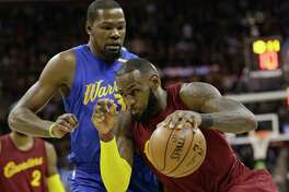 FILE - In this Dec. 25, 2016, file photo, Cleveland Cavaliers' LeBron James drives against Golden State Warriors' Kevin Durant during an NBA basketball game in Cleveland. Now, as James, Durant and their teammates wait on the next opponent for the respective conference finals, the world is watching as they move their unblemished, 8-0 teams ever closer to an anticipated Cavs-Warriors rematch that might finally come to fruition at last in a matter of weeks. (AP Photo/Tony Dejak, File)