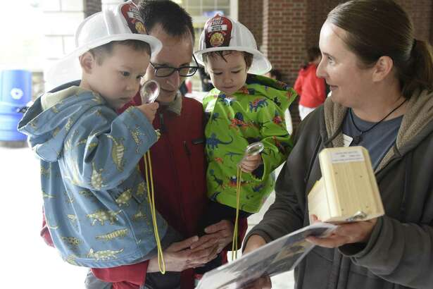 Audubon Greenwich Education Coordinator Susan Mathews shows a birdhouse to Greenwich resident Tom Meyer and his children Del Changmeyer, left, 3, and Sofia Changmeyer, 3, at the Junior League of Greenwich Touch a Truck event at Town Hall in 2016. The annual event will return on June 4, rain or shine.