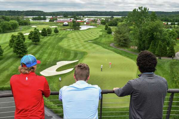 Spectators watch golfers practicing at the Trump National Golf Club.