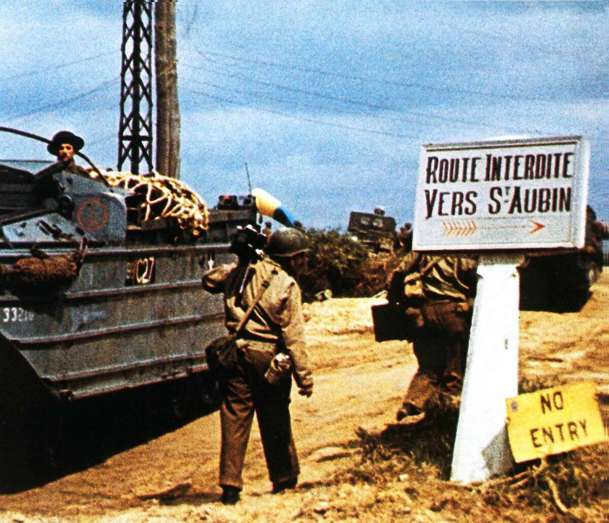 The road to Saint-Aubin-sur Mer has been closed due to fighting in the area. June 1944. Without much success the German Army was trying to prevent the Royal Marines from establishing contact with the British 3rd Division on Juno Beach. To the left is an amphibious vehicle (DUKW). Next to it is a camera man from the team of George Stevens. Normandy, France. (Photo by Galerie Bilderwelt/Getty Images)