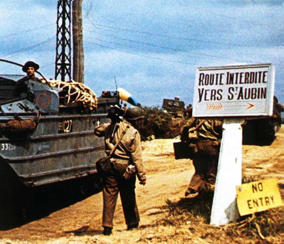 The road to Saint-Aubin-sur Mer has been closed due to fighting in the area. June 1944. Without much success the German Army was trying to prevent the Royal Marines from establishing contact with the British 3rd Division on Juno Beach. To the left is an amphibious vehicle (DUKW). Next to it is a camera man from the team of George Stevens. Normandy, France.  (Photo by Galerie Bilderwelt/Getty Images) Photo: Galerie Bilderwelt/Getty Images