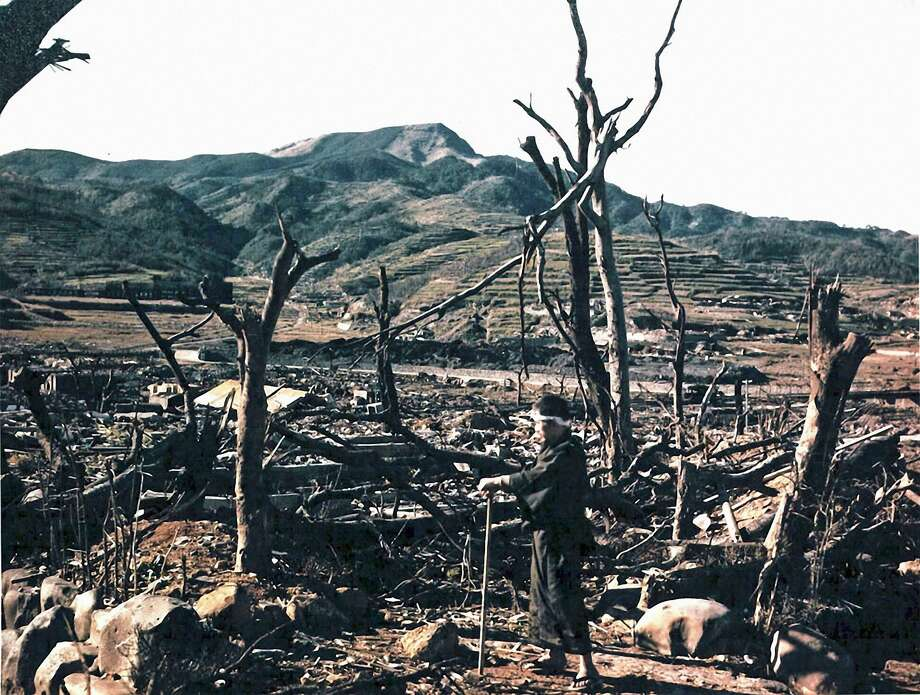 """Dr. Takashi Nagai of Nagasaki Hospital inspecting damage caused by the atomic bomb in the Matsuyama District. August 1945. The ruins of the Nagasaki Medical College, where he had worked as a radiologist since 1928, are behind the trees in the center right Dr. Nagai would die of radiation poisoning a few days after this photo was taken. His residence was turned into a museum. Dr. Nagai is known as the """"Saint of Urakami"""" and the """"Gandhi of Nagasaki."""" Nagasaki, Japan. (Photo By Galerie Bilderwelt/Getty Images) Photo: Galerie Bilderwelt/Getty Images"""