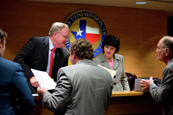 Commissioner Wayne Christian and Chairman Christi Craddick sign orders after a Texas Railroad Commission conference this month. Women occupy eight of the 15 top leadership positions - excluding the three elected commissioners - at the commission.