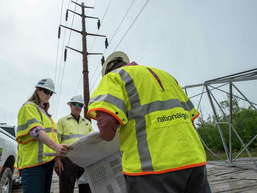 National Grid workers; Jennifer Schlegel, project manager , left George Breen, construction supervisor, center and Patrick Stella, communications look over plans for the new cable and weathering steel uprights at the new construction on the power line upgrade by National Grid on Paterson Road in Tuesday May 23, in Greenwich, N.Y. (Skip Dickstein/Times Union)