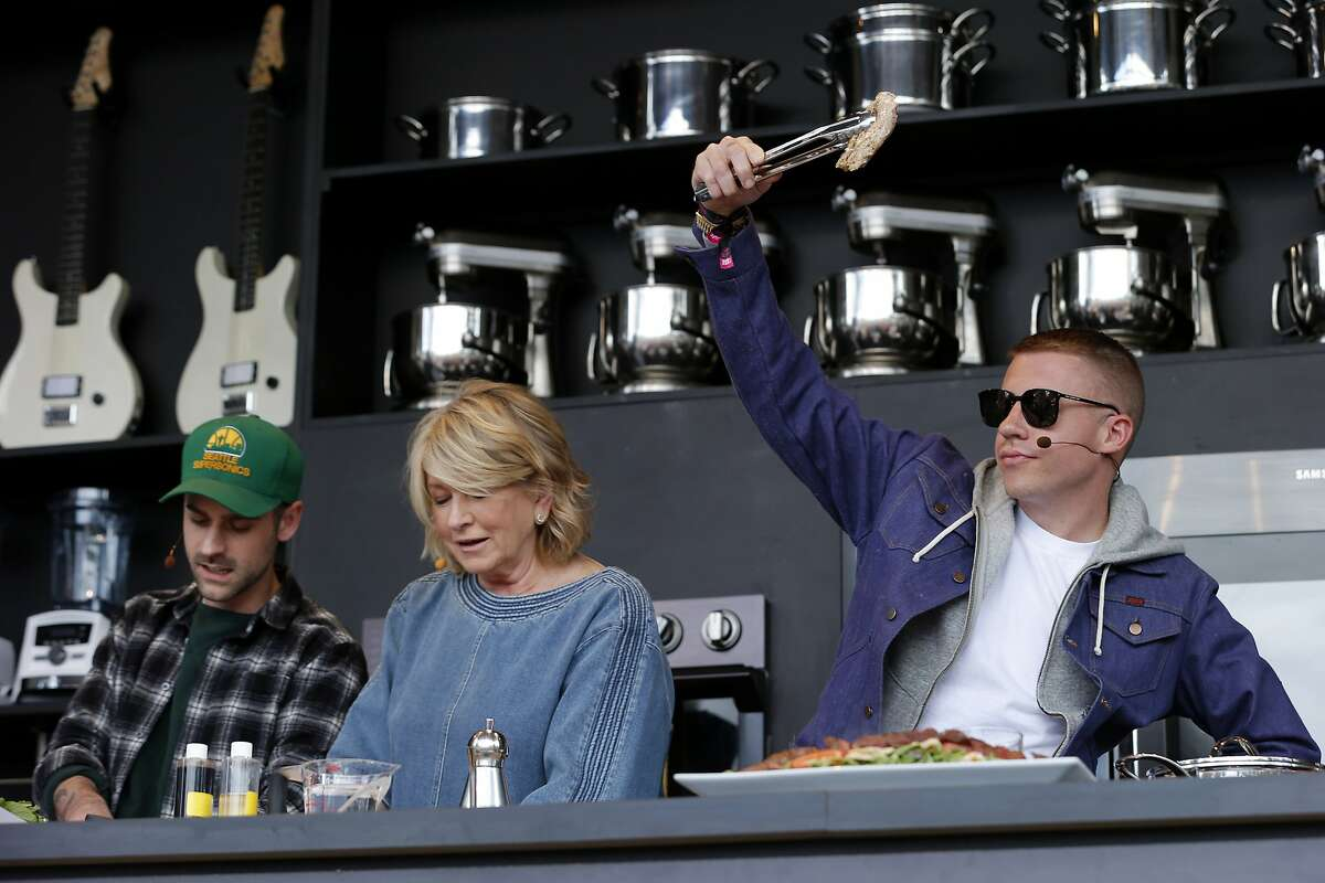 From right: Macklemore holds a piece of chicken as he cooks with Martha Stewart and Ryan Lewis during BottleRock.