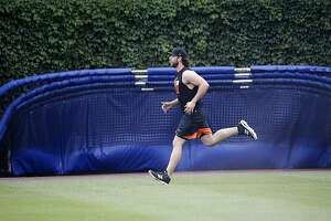 San Francisco Giants' Madison Bumgarner runs in right field of Wrigley Field before a baseball game between the Chicago Cubs and Giants Thursday, May 25, 2017, in Chicago. Bumgarner, has been on the disabled list since suffering a sprained AC joint in his pitching shoulder along with bruised ribs after a dirt bike accident earlier this season. (AP Photo/Charles Rex Arbogast)
