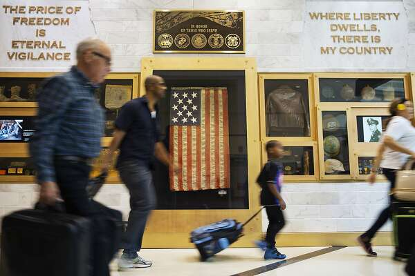 An American flag from the Spanish-American war hangs as part of a display paying tribute to U.S. armed forces as travelers pass through Hartsfield-Jackson Atlanta International Airport in Atlanta at the beginning of the Memorial Day weekend Friday, May 26, 2017. (AP Photo/David Goldman)