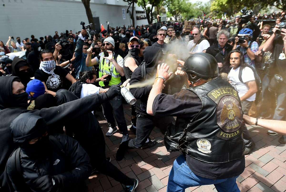 A man gets sprayed with a chemical irritant as multiple fights break out between Trump supporters and anti-Trump protesters in Berkeley, California on April 15, 2017. Hundreds of people with opposing opinions on President Donald Trump threw stones, lit fires, tossed explosives and tear gas and attacked each other with makeshift weapons as police stood by. / AFP PHOTO / Josh EdelsonJOSH EDELSON/AFP/Getty Images
