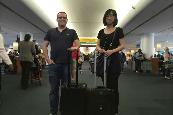 Associated Press journalists Scott Mayerowitz and Candice Choi wait at New York's LaGuardia Airport. They were traveling together to compare the experiences of travelers with elite status and those without.