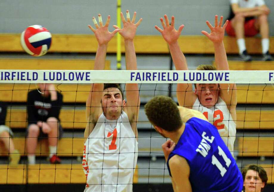 Darien's Alex Preston spikes the ball past Ridgefield's Myles Peckham, left, and Jack Lincoln, right, during FCIAC boys volleyball championship action in Fairfield, Conn. on Friday May 26, 2017. Photo: Christian Abraham / Hearst Connecticut Media / Connecticut Post