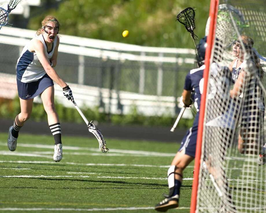 Immaculate's Megan Mitchell scores a goal, firing the ball past Staples goalie Panagiota Tsilfides, during their State Division II quarterfinal match Monday at Immaculate High. Photo: Barry Horn / The News-Times Freelance