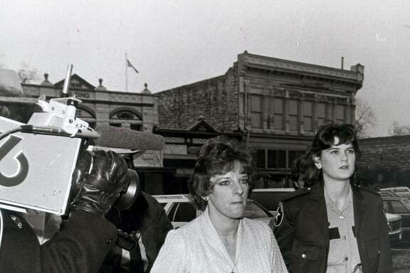 Genene Jones arrives at Williamson County Courthouse accompanied by a deputy. Georgetown Texas. 1/16/84 Express-News file photo