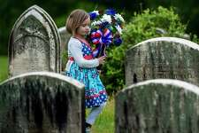 Quincy Gagliardi, 5 of Watervliet assists her mother, florist Lauren Gagliardi of The Flower Girl florist shop in putting out arrangements for clients for Memorial Day at the Albany Rural Cemetery Friday May 26, 2017 in Menands, N.Y.  (Skip Dickstein/Times Union)
