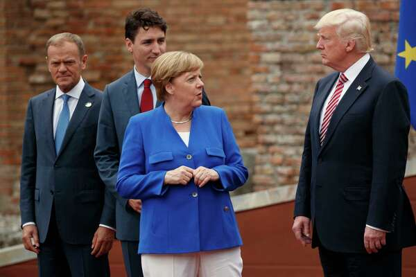 German Chancellor Angela Merkel talks with President Donald Trump during a family photo with G7 leaders at the Ancient Greek Theater of Taormina, during the G7 Summit, Friday, May 26, 2017, in Taormina, Italy. From left, European Council President Donald Tusk, Canadian Prime Minister Justin Trudeau, Merkel, and Trump. (AP Photo/Evan Vucci)