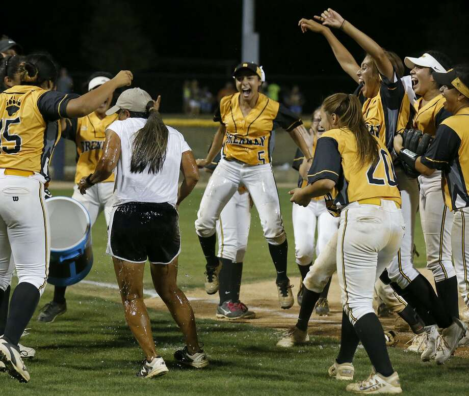 Members of the Brennan Bears celebrate after dousing head coach Ruby de la Garza with water after Game 2 of their Region IV-6A final series against New Braunfels Canyon at St. Mary's University on May 26, 2017. Photo: Edward A. Ornelas /San Antonio Express-News / © 2017 San Antonio Express-News
