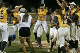 The Brennan softball team celebrates after dousing coach Ruby de la Garza with water, after Game 2 of their Region IV-6A final.