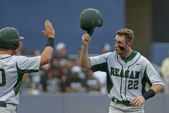 Reagan's Porter Brown (left) congratulates Cade Bormet after he scored during Game 2 of a Region IV-6A semifinal series against Southwest on May 26, 2017, at the SAISD Complex.