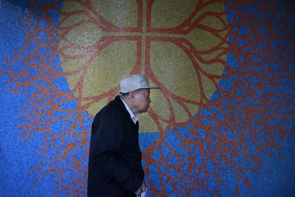 """A man walks past Ruth Asawa's """"Growth Mosaic"""", 1969 in front of  Bethany Center Senior Housing on Thursday, June 20, 2013 in San Francisco,  Calif."""