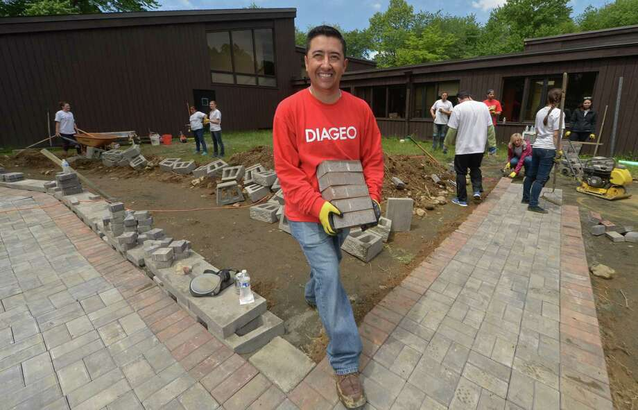 More than 110 employees from Diageo North America's finance team including Juan Vallejo return to STAR on Wednesday, May 24, to complete phase two of a transformational service project at the STAR, Inc. Lighting the Way Center in Norwalk. The crew's worked on extending a brick handicapped walkway, constructing a patio around the new STAR greenhouse, creating raised beds for a wheelchair-accessible herb, vegetable and flower garden, fencing it in and adding decorative mulch and specimen landscape plantings. STAR is a nonprofit organization that has provided services to individuals with developmental disabilities in mid-Fairfield County since 1952. Photo: Erik Trautmann / Hearst Connecticut Media / Norwalk Hour
