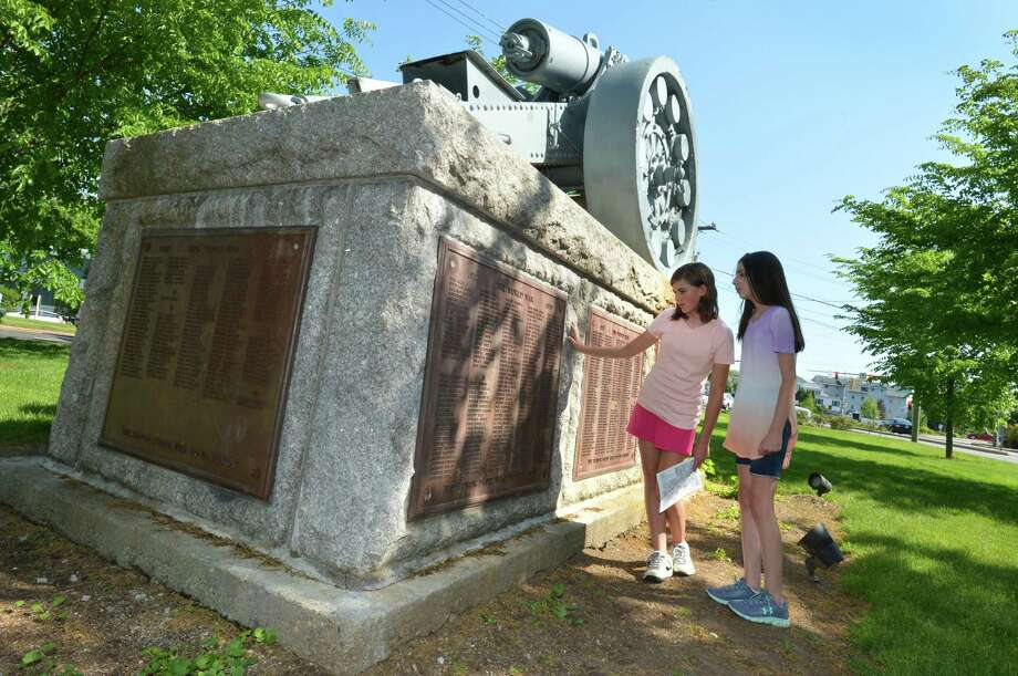 "Seventh-graders at Roton Middle School Kelsey McClung and Claire DiChiaro read some of the veterans names off the plaque on the cannon pedestal at Norwalk's Historic Town Green on Wednesday, May 17, in Norwalk. Students in Dean Vaccaros seventh- and- eighth-grade American History classes at Roton Middle School have been sent on a journey across the city to visit various war memorials in honor of Memorial Day to learn more about the monument's historical importance. Vaccaros project, ""Beyond Names on a Wall — Remembering Norwalk's Fallen Soldiers,"" gives students one month to visit four locations such as the Green, the Veterans' Wall at City Hall, and the Shea-MaGrath Memorial at Calf Pasture Beach. Photo: Alex Von Kleydorff / Hearst Connecticut Media / Norwalk Hour"