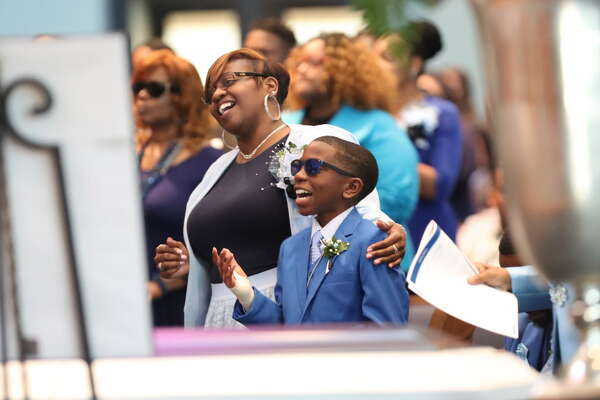 April and her surviving son, Adrian, give praise during the Mitchell funeral for Terrance, Kaila and Kyle. (Steve Gonzales / Chronicle)