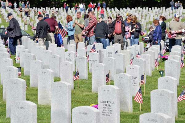 Hundreds of volunteers turn out to place American flags on over 15,000 graves for Memorial Day weekend at Saratoga National Cemetery Saturday May 27, 2017 in Schuylerville, NY.  (John Carl D'Annibale / Times Union)