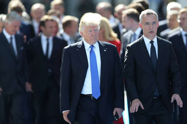 U.S. President Donald Trump, left, and with NATO Secretary General Jens Stoltenberg in front of other world leaders at NATO headquarters in Brussels, Belgium, on May 25, 2017. (