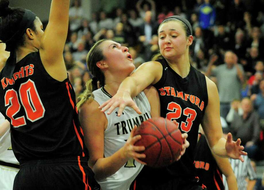 Trumbull's Claudia Tucci is blocked by Stamford's Alexa Kellner as she attempts a basket during FCIAC Girls Basketball Championship action in Fairfield, Conn., on Friday Feb. 23, 2017. Defending at left is Stamford's Marthe Guirand. Photo: Christian Abraham / Hearst Connecticut Media / Connecticut Post