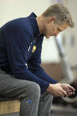Golden State Warriors head coach Steve Kerr checks his phone following a practice session Saturday, May 27, 2017 in Oakland, Calif., as they prepare for the NBA Finals against the Cleveland Cavaliers