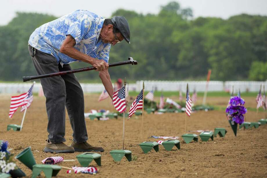 Phillip Suarez, a Marine Corps veteran, uses his cane to tap in an American flag that had fallen over in front of the temporary grave marker for his brother-in-law Genaro Rincon in the section of Fort Sam Houston National Cemetery where recently deceased veterans are interred. Rincon, who was interred May 9, was one of the more than 2400 names the American Legion read aloud at Fort Sam Houston National Cemetery in San Antonio, Texas on May 27, 2017. Ray Whitehouse / for the San Antonio Express-News Photo: Ray Whitehouse, Photographer / For The San Antonio Express-News
