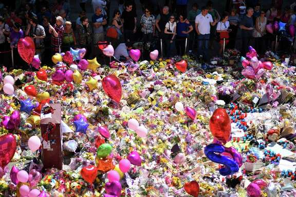 "A carpet of messages of support and floral tributes to the victims of the Manchester attack lies in St Ann's Square in Manchester on May 27, 2017. British police said they arrested two more people during raids Saturday in connection with the suicide bombing at a Manchester concert, with a ""large part"" of the network behind the attack now being held. / AFP PHOTO / Ben STANSALLBEN STANSALL/AFP/Getty Images"