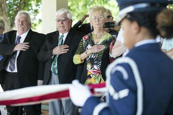 David Taylor, second left, and his wife Janet Taylor, hold their hands to their hearts as members of the honor guard fold the flag over the ashes of David's uncle, the centenarian Air Force Lt. Col. Glenn W. Taylor who fought in WWII, Korea and Vietnam during his funeral at Fort Sam Houston National Cemetery in San Antonio, Texas on Wednesday, May 24, 2017.