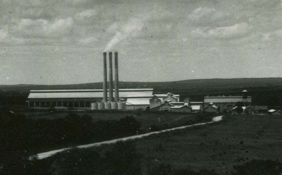 This archival photo shows the exterior of the San Antonio Portland Cement Company with its three smokestacks, which still tower over the Alamo Quarry market today. This photo was published Dec. 26, 1926, in the San Antonio Light. Photo: /Courtesy UTSA Special Collections