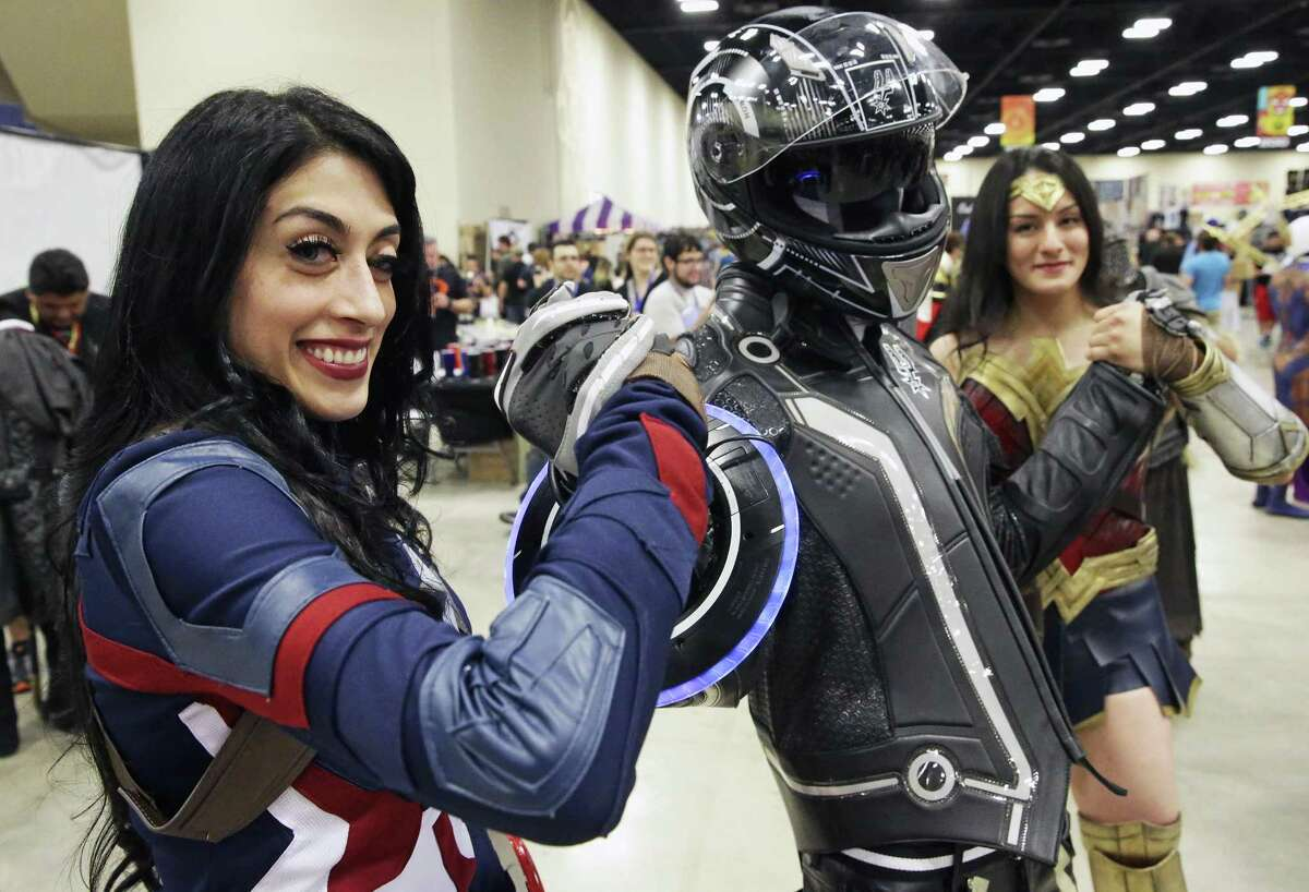 Cecilia Bermudez (left) as Captain America holds up Mike Smith with Maria Bermudez as Wonder Woman on the other hand at the Alamo City Comic Con at the Henry B. Gonzalez Convention Center on May 27, 2017.