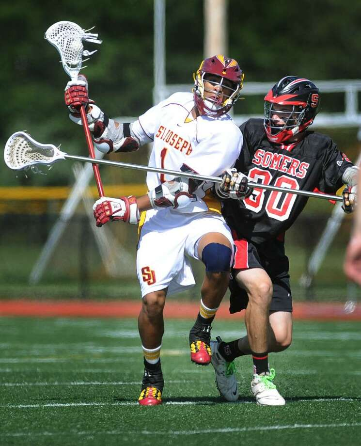 St. Joseph's Lance Hunt protects the ball Somers defender Garrett Ficara during Monday's matchup in the state championship lacrosse playoffs at St. Joseph High School in Trumbull. Photo: Brian A. Pounds / Connecticut Post