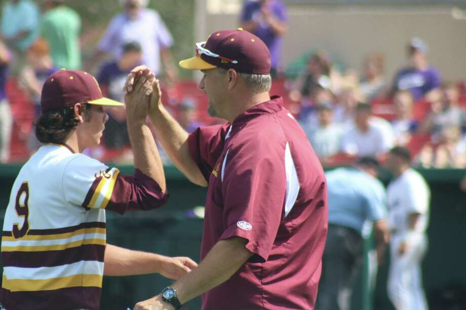 Pitching coach Donnie Elliott congratulates Clay Aguilar and his complete-game victory Saturday afternoon as the Deer celebrate their berth in the Region III title round for the second straight season. Photo: Robert Avery