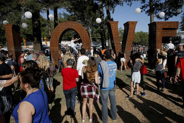 Festival-goers are seen checking out Laura Kimpton's LOVE sculpture during BottleRock on Saturday, May 27, 2017, in Napa, Calif.
