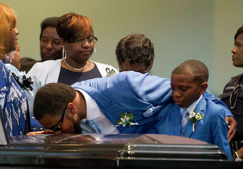 Adrian Mitchell, right, watches as his father Terrance Mitchell, Sr., kisses one of the three caskets of his siblings Terrance Jr., Kaila and Kyle during a funeral service at Christ United Methodist Church for the three Mitchell children who died in a May 12 house fire in the community of Tamina Saturday. Photo: Jason Fochtman, Staff Photographer / © 2017 Houston Chronicle