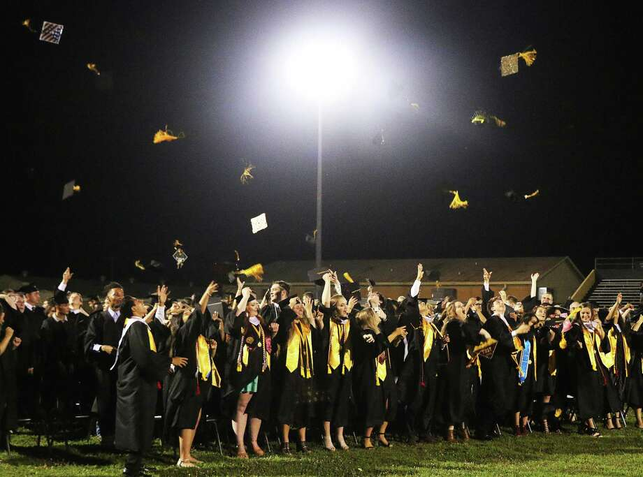 Class members celebrate their graduation from Liberty High School Saturday night by tossing their tassels and mortarboards into the sky following the school song. Photo: David Taylor