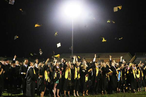 Class members celebrate their graduation from Liberty High School Saturday night by tossing their tassels and mortarboards into the sky following the school song.