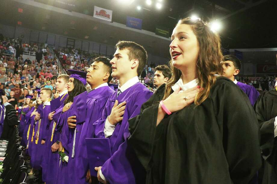Graduates recite the Pledge of Allegiance together with faculty members for the last time as students of Dayton High School. Photo: David Taylor