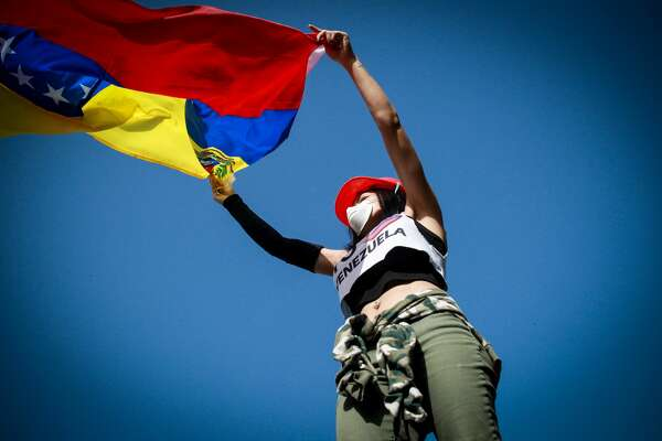 An opposition activist waves a Venezuelan national flag during clashes with the riot police during a demonstration against Venezuelan President Nicolas Maduro in Caracas, on May 26, 2017. Both the Venezuelan government and the opposition admit that violent protests that have gripped the country for nearly two months are out of control -- and analysts warn they could be a double-edged sword that might trigger even more unrest. (Photo by Elyxandro Cegarra/NurPhoto via Getty Images)