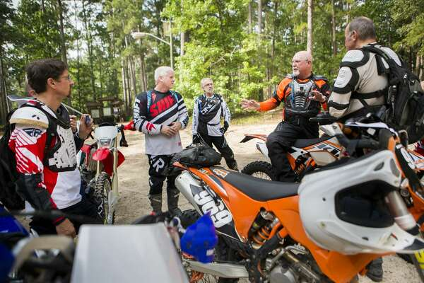 Larry Fulk, right, a member of the Old Dudes On Dirt Bikes group talks about a plan to join search efforts to find three-year-old Ezra who went missing at the Sam Houston National Forest on Saturday afternoon. The group found out about the efforts when they arrived to the forest to ride their bikes for recreation, Sunday, May 28, 2017, in Waverly. ( Marie D. De Jesus / Houston Chronicle )