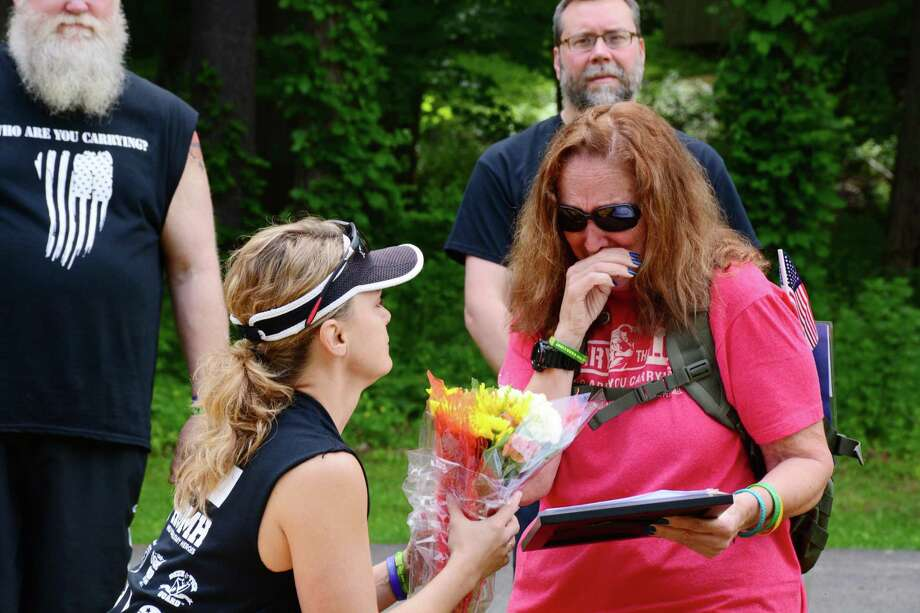 """Harrybrooke Park in New Milford honored fallen military heroes at the """"Who Are You Carrying"""" event on Sunday, May 28, 2017.  The event recognized Petty Officer First Class Jason D. Lewis, from Brookfield. Valerie Lewis, Asst. Executive Director of the park, offers a bouguet of flowers to Lewis' mom, Jean Mariano of New Milford. Photo: Lisa Weir / For Hearst Connecticut Media / The News-Times Freelance"""