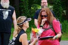 """Harrybrooke Park in New Milford honored fallen military heroes at the """"Who Are You Carrying"""" event on Sunday, May 28, 2017.  The event recognized Petty Officer First Class Jason D. Lewis, from Brookfield. Valerie Lewis, Asst. Executive Director of the park, offers a bouguet of flowers to Lewis' mom, Jean Mariano of New Milford."""