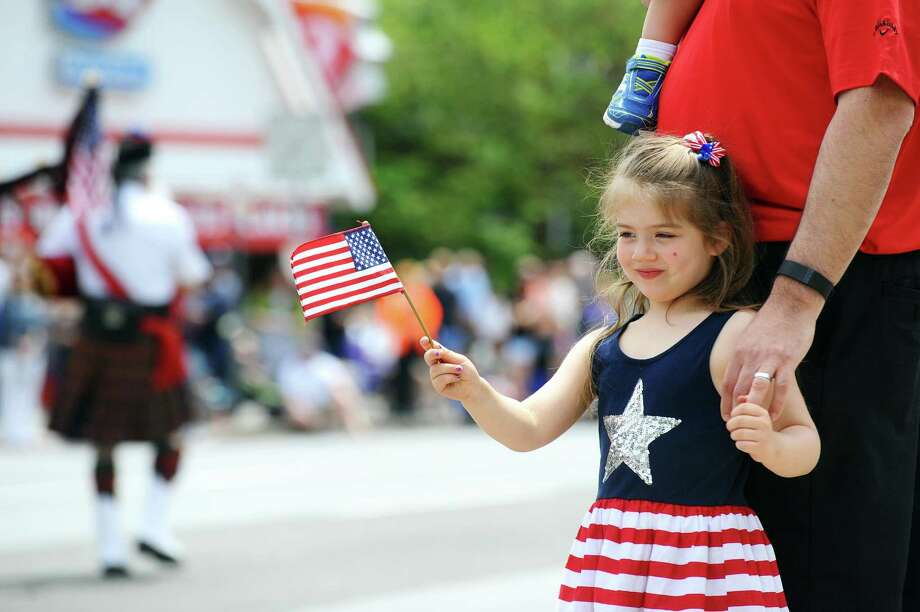 Zoe Paksi, 4, of Stamford, waves an American flag while watching bagpipers march on Summer Street during the Memorial Day Parade in Stamford on Sunday. Photo: Michael Cummo / Hearst Connecticut Media / Stamford Advocate
