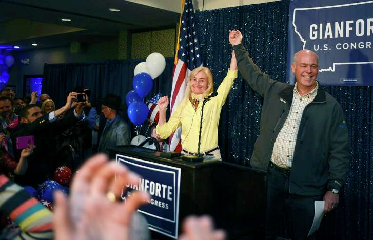 Greg Gianforte, right, and wife Susan, center, celebrate his win over Rob Quist for the open congressional seat at the Hilton Garden Inn Thursday night, May 25, 2017, in Bozeman, Mont. Gianforte, a technology entrepreneur, defeated Democrat Quist to continue the GOP's two-decade stronghold on the congressional seat.  (Rachel Leathe/Bozeman Daily Chronicle via AP)