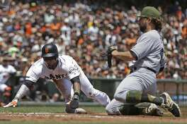 San Francisco Giants' Eduardo Nunez, left, slides to score on a wild pitch by Atlanta Braves pitcher R.A. Dickey, right, in the first inning of a baseball game Sunday, May 28, 2017, in San Francisco. (AP Photo/Ben Margot)