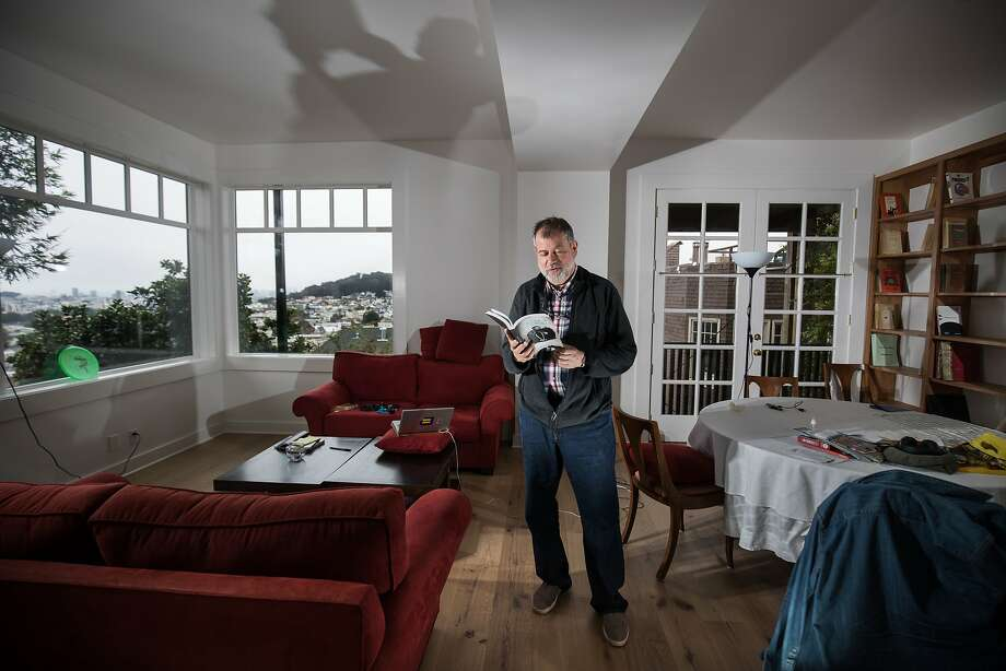 """Martin Winckler flips through his novel, """"The Case of Dr. Sachs,"""" in his artist's residence, a newly renovated in-law unit beneath the French consul's residence. Photo: Paul Kuroda"""
