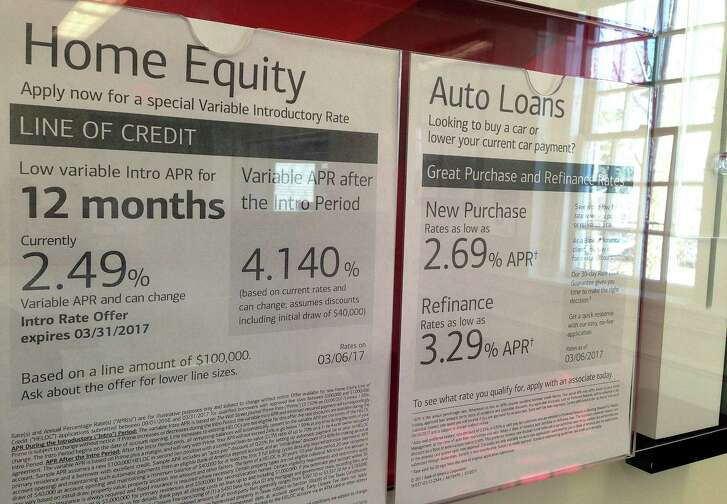 FILE - In this March 6, 2017, file photo, home equity loan rates are among the loan rates displayed at a bank in North Andover, Mass. U.S. housing equity now equals 58 percent of home values, the highest such point since 2006. Yet borrowing against that equity has barely budged from post-recession lows, which helps explain why consumer spending remains weak eight years after the Great Recession ended. (AP Photo/Elise Amendola, File)